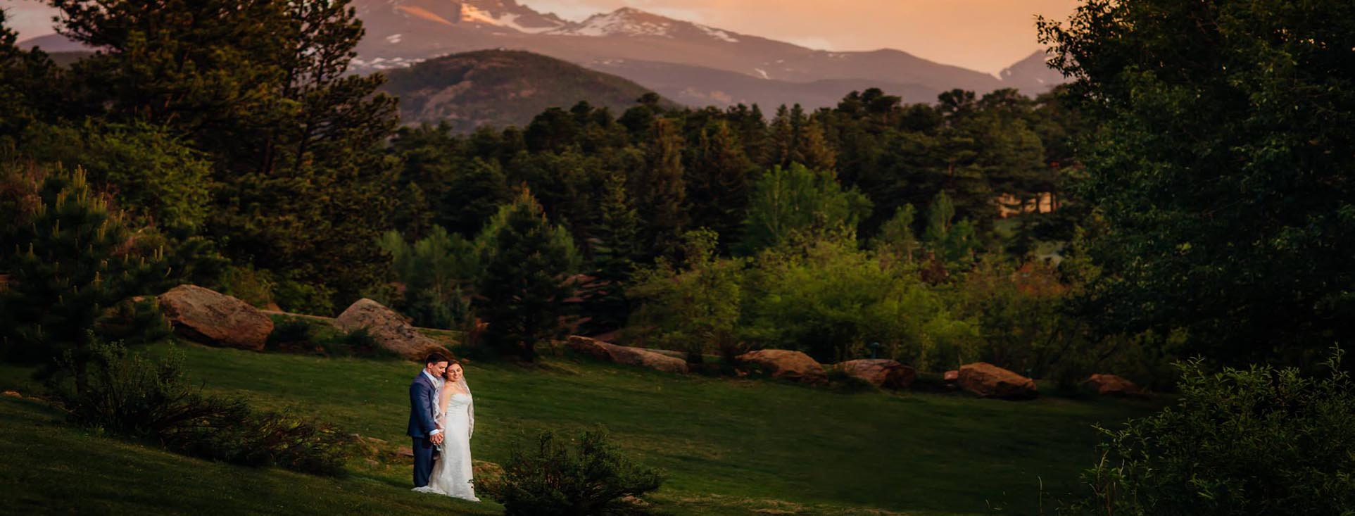 wedding couple outside with mountains behind them.